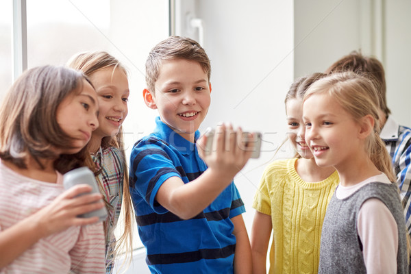 group of school kids with smartphone and soda cans Stock photo © dolgachov