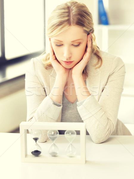pensive businesswoman with sand glass Stock photo © dolgachov