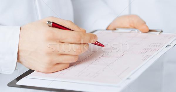 Férfi orvos kezek tart kardiogram fényes kép Stock fotó © dolgachov