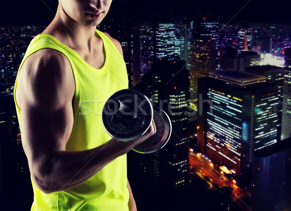 close up of young man with dumbbell flexing biceps Stock photo © dolgachov