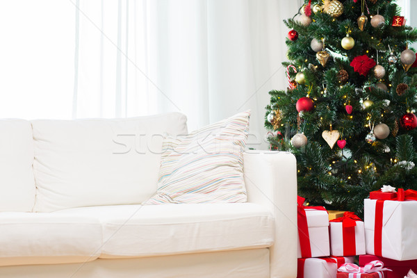 christmas tree, gift boxes and sofa at home room Stock photo © dolgachov