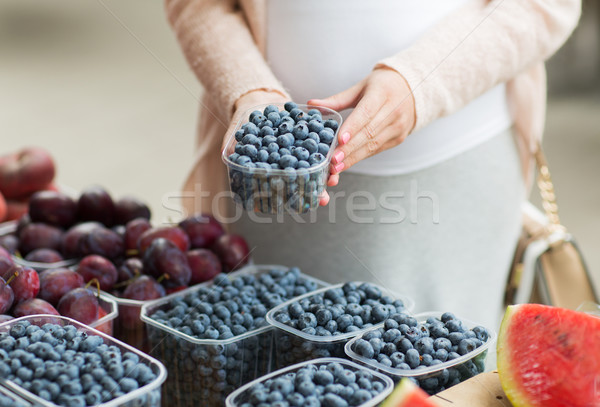 pregnant woman buying blueberries at street market Stock photo © dolgachov