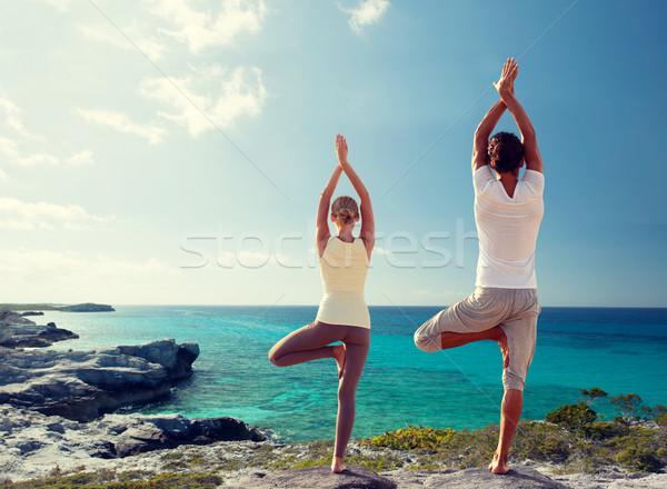 couple making yoga exercises on beach from back Stock photo © dolgachov