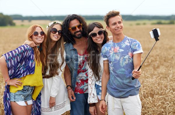 hippie friends with smartphone on selfie stick Stock photo © dolgachov