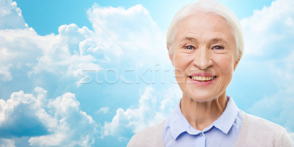 happy senior woman face over blue sky and clouds Stock photo © dolgachov