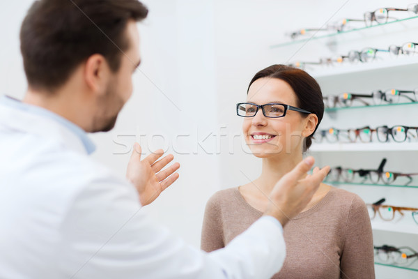 optician and woman in glasses at optics store Stock photo © dolgachov