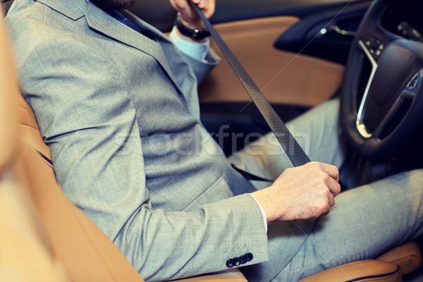 close up of man fastening seat safety belt in car Stock photo © dolgachov