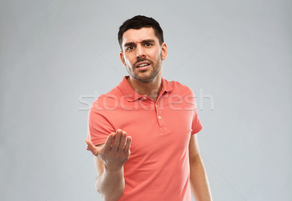 arguing man proving something over gray Stock photo © dolgachov