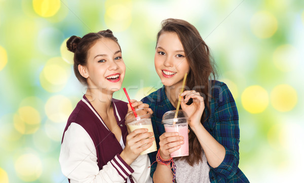 Stock photo: happy pretty teenage girls drinking milk shakes