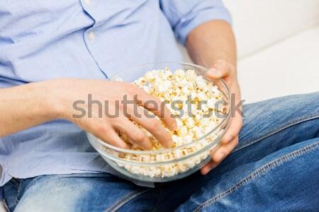 close up of man eating popcorn at home Stock photo © dolgachov