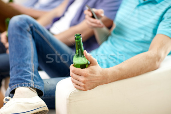 close up of male friends drinking beer at home Stock photo © dolgachov