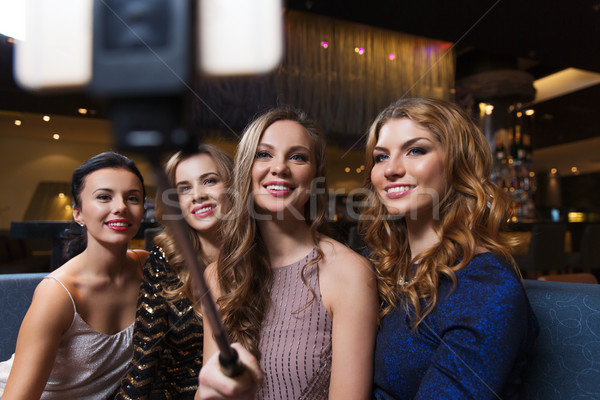 women with smartphone selfie stick at night club Stock photo © dolgachov