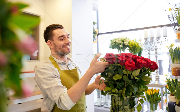 smiling florist man with roses at flower shop Stock photo © dolgachov