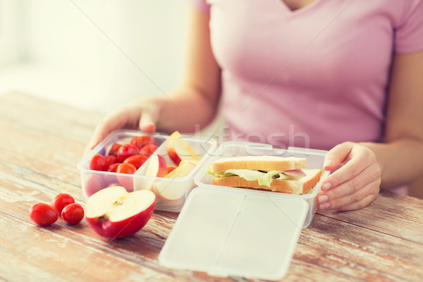 close up of woman with food in plastic container Stock photo © dolgachov