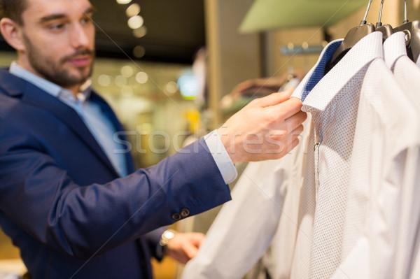 close up of man choosing shirt in clothing store Stock photo © dolgachov