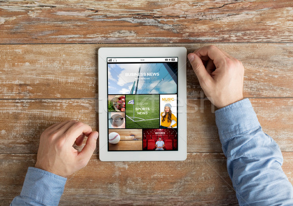 close up of male hands to tablet pc on table Stock photo © dolgachov