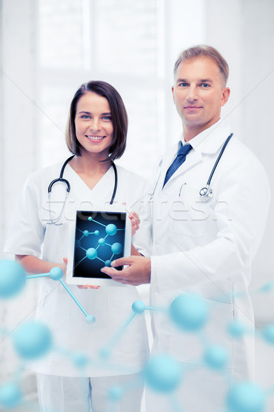 two doctors showing tablet pc with molecules Stock photo © dolgachov