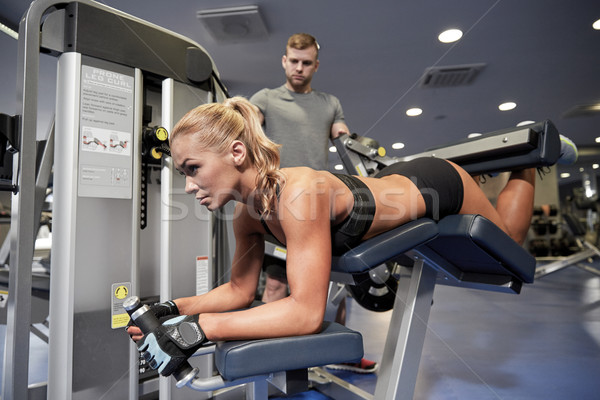 man and woman flexing muscles on gym machine Stock photo © dolgachov