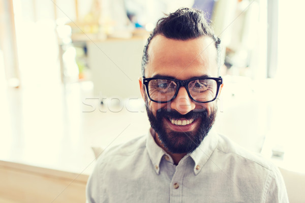 smiling man with eyeglasses and beard at office Stock photo © dolgachov