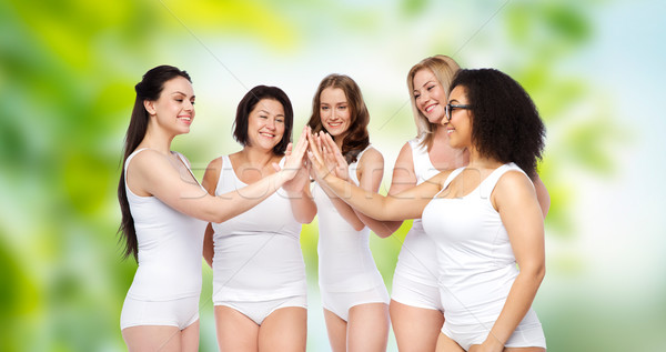 Stock photo: group of happy different women making high five