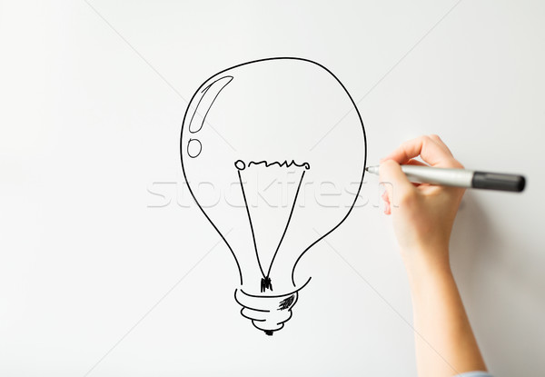 close up of hand drawing light bulb on white board Stock photo © dolgachov