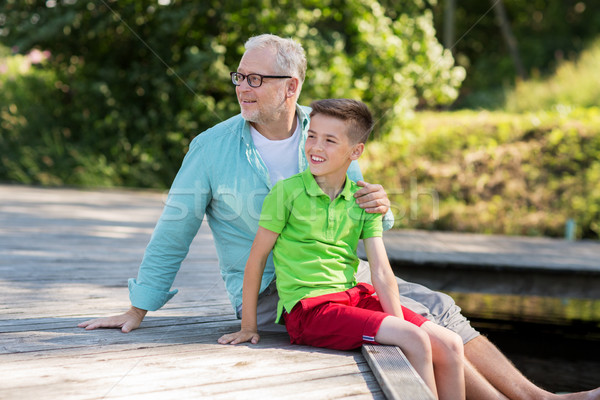 grandfather and grandson sitting on river berth Stock photo © dolgachov