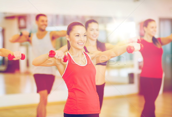 group of smiling people working out with dumbbells Stock photo © dolgachov