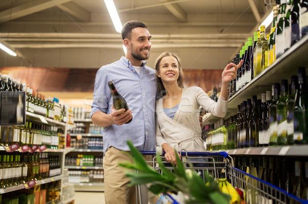couple with wine and shopping cart at liquor store Stock photo © dolgachov