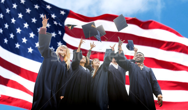happy students throwing mortarboards up Stock photo © dolgachov