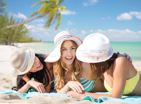 group of happy women in hats sunbathing on beach Stock photo © dolgachov