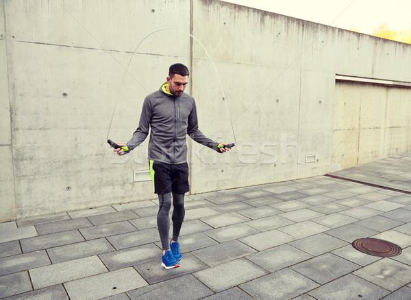 man exercising with jump-rope outdoors Stock photo © dolgachov