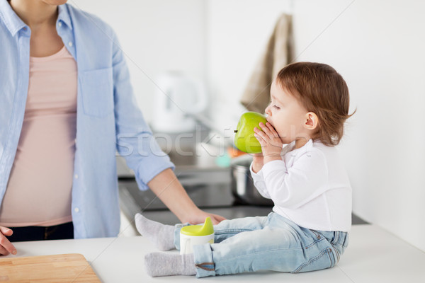 mother and baby eating green apple at home kitchen Stock photo © dolgachov