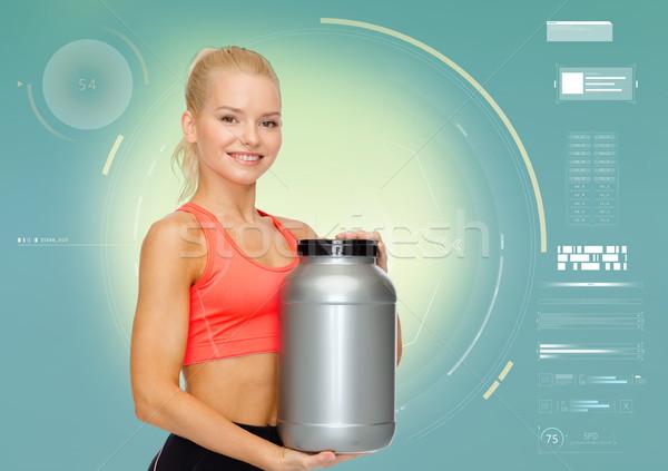 smiling sporty woman with sports nutrition jar Stock photo © dolgachov