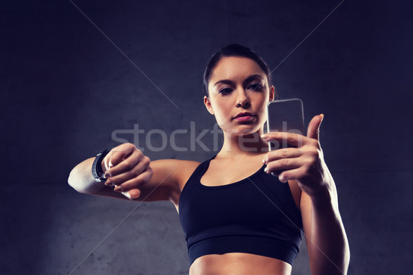 woman with heart-rate watch and smartphone in gym Stock photo © dolgachov