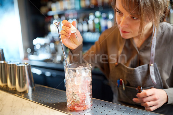 bartender adding essence to cocktail glass at bar Stock photo © dolgachov