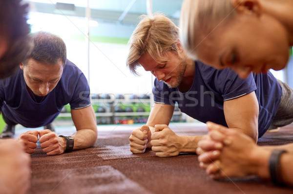 group of people doing plank exercise in gym Stock photo © dolgachov