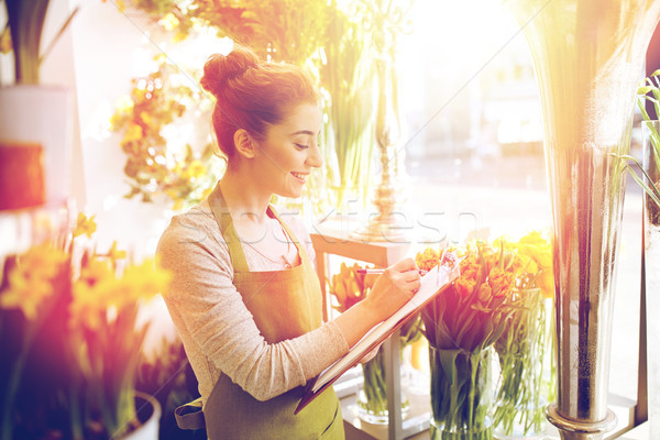 florist woman with clipboard at flower shop Stock photo © dolgachov