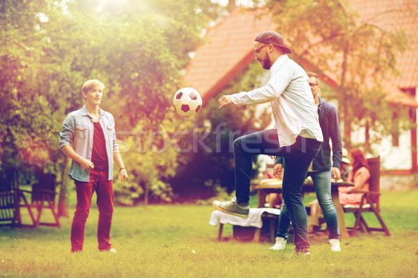 happy friends playing football at summer garden Stock photo © dolgachov