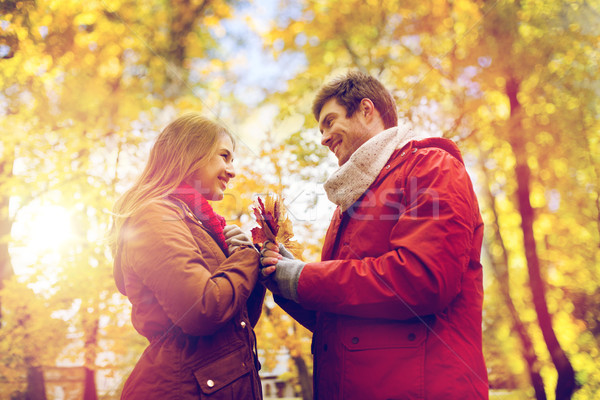happy couple with maple leaves in autumn park Stock photo © dolgachov