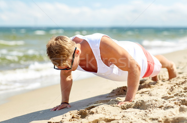 young man doing push-ups on summer beach Stock photo © dolgachov