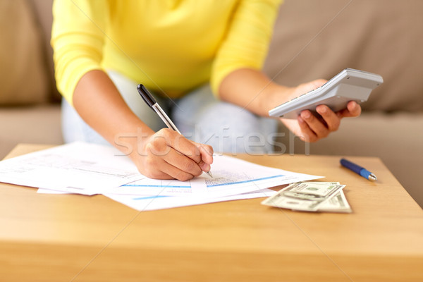 woman with money, papers and calculator at home Stock photo © dolgachov