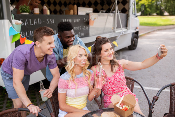 happy young friends taking selfie at food truck Stock photo © dolgachov
