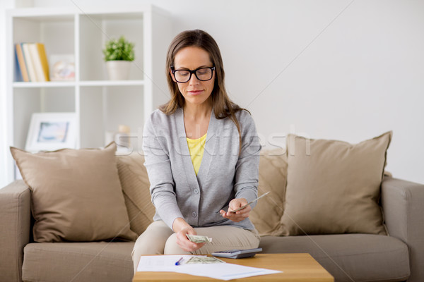 woman with papers counting money at home Stock photo © dolgachov