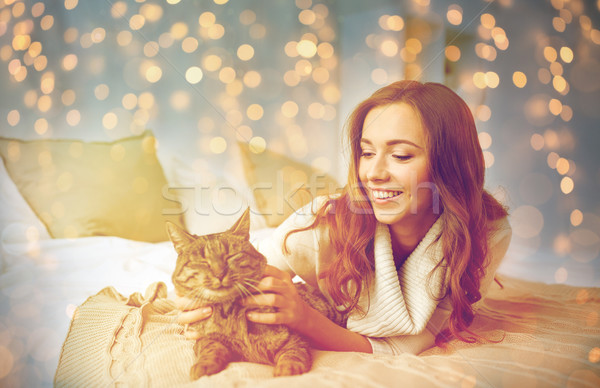 happy young woman with cat lying in bed at home Stock photo © dolgachov