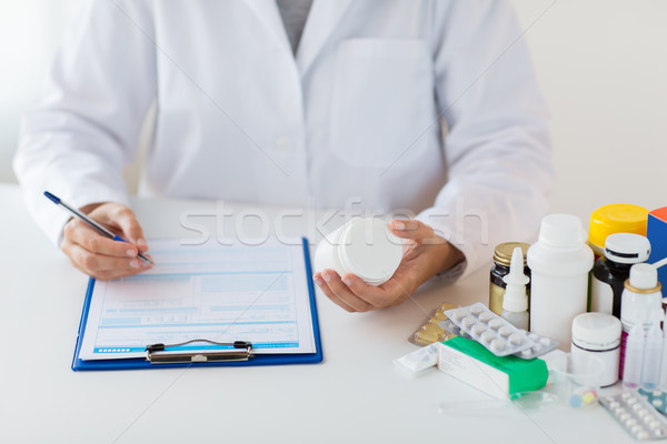 doctor with medicines and clipboard at hospital Stock photo © dolgachov