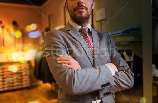 close up of man in suit and tie at clothing store stock