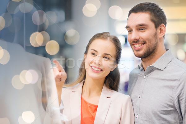 happy couple pointing finger to shop window Stock photo © dolgachov