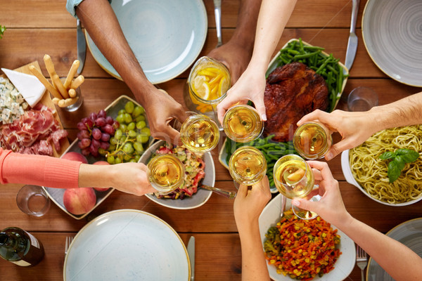 hands clinking wine glasses over table with food Stock photo © dolgachov