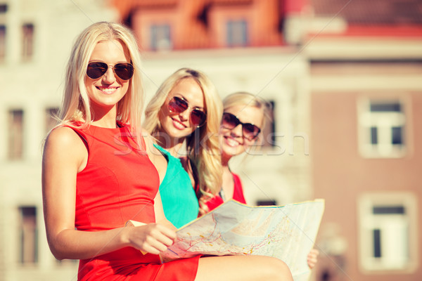 beautiful three women with tourist map in the city Stock photo © dolgachov