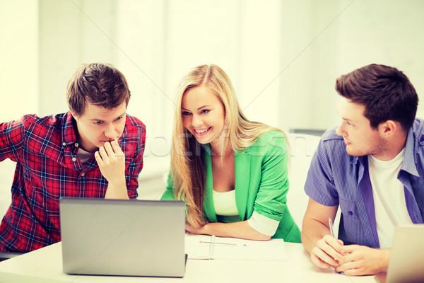 Sonriendo estudiantes mirando portátil escuela educación Foto stock © dolgachov